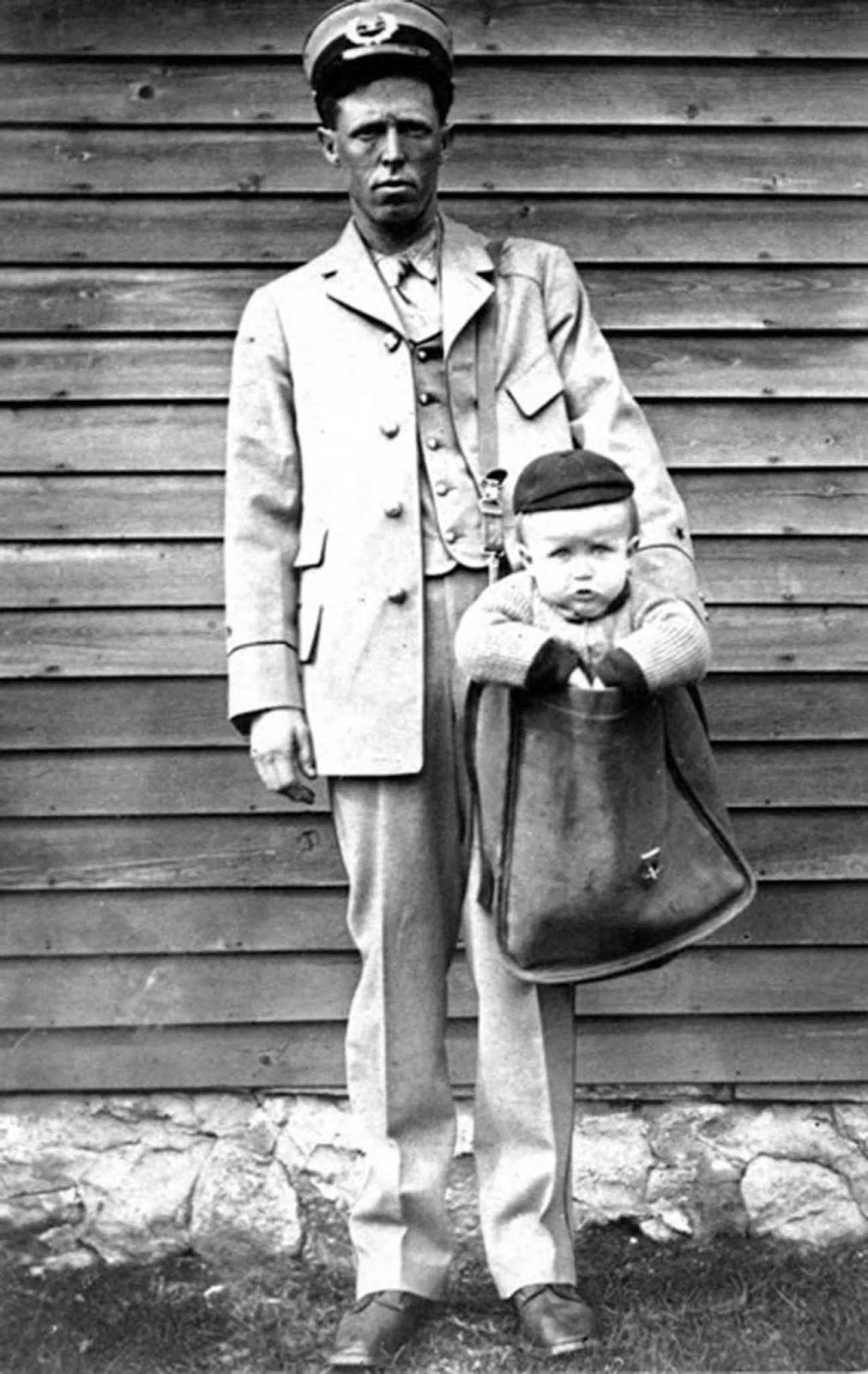 A mailman with a baby (most likely a stage photograph).